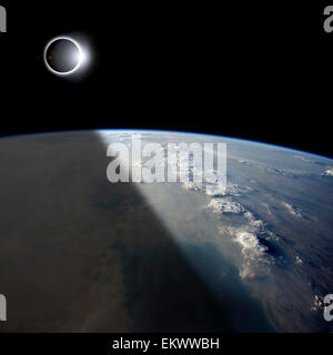A solar eclipses partially shades the Earth below while the emerging sun lights the remainder of the planet. - Stock Image