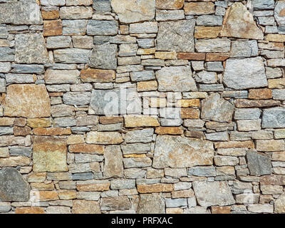 Stone granite wall made of stacked pieces stones. Full frame image as background. - Stock Image