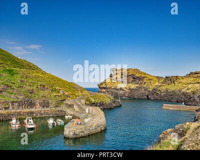 2 July 2018: Boscastle, Cornwall, UK - A couple admire the view of the harbour and its stunning rock formations from the breakwater. - Stock Image