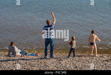 Sidmouth, UK. 21st Oct 2018. Unprecedented weather in Devon brought many families flocking to Sidmouth beach,sunbathing in high temperatures and throwing pebbles into the sea. Photo Central/Alamy Live News - Stock Image