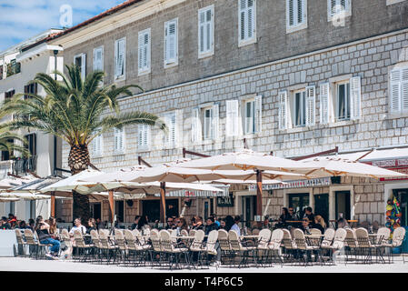 Montenegro, Tivat, April 9, 2019: People sit, eat and communicate with each other in a street cafe. - Stock Image