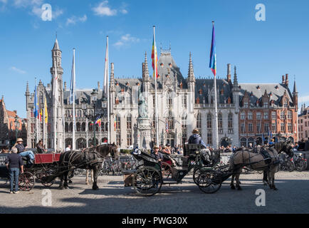 Horse drawn carriages waiting for tourists, with Provincial Court and Historium buildings in historic medieval city of Bruges, West Flanders, Belgium - Stock Image