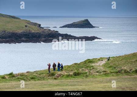 A family standing on the coast path overlooking Crantock Beach in Newquay in Cornwall. - Stock Image