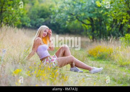Pretty teenager girl countrygirl siting on countryside wearing Summer clothes Pink tshirt flowery mini-skirt and sneakers - Stock Image