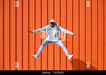Man wearing casual denim clothes jumping in the air in front of orange wall - Stock Image