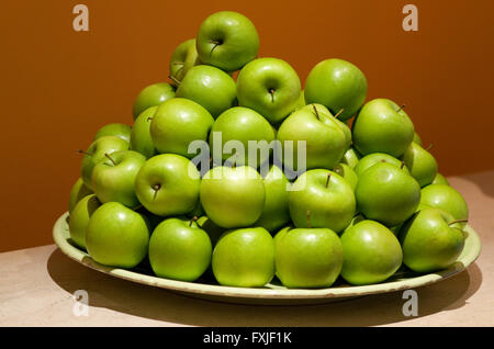 Pile of green apples on a plate. - Stock Image