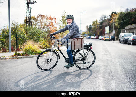 An active senior man with helmet and electrobike cycling outdoors in autumn in town. - Stock Image