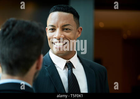 Businessman talking with his colleague in hotel - Stock Image