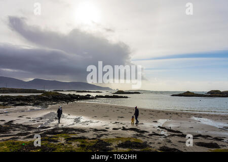 Rosbeg, County Donegal, Ireland. 17th March 2019. A family take a walk on the beach on a day of sunshine and showers on the north-west coast. Credit: Richard Wayman/Alamy Live News - Stock Image