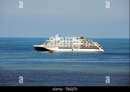 Cruise ship at sea, large luxury white cruise ship liner on blue sea water and blue sky background.Small watertaxi transporting passengers to the shor - Stock Image