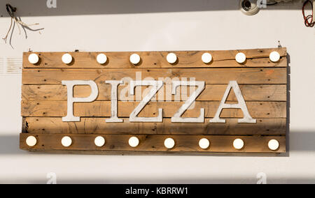 Pizza sign made of wooden planks and light bulbs on top and bottom - Stock Image