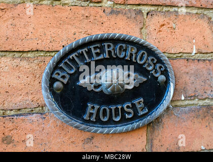 Smart ornate oval cast metal house sign for Buttercross House mounted on old red brick wall, Oakham, Rutland, Leicestershire, England, UK - Stock Image