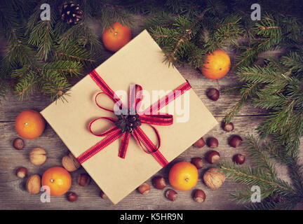 Christmas composition with a gift box, tangerines, nuts and spices. view from above - Stock Image