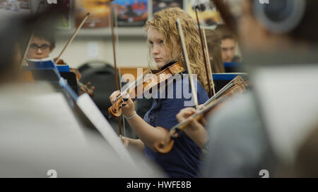 Selective focus view of serious teenage girl musician playing violin in band class - Stock Image