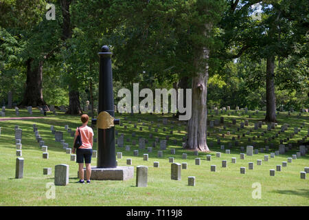 A tourist views a cemetery marker made of a cannon barrel in the Shiloh Nat. Cemetery, Tennessee. - Stock Image