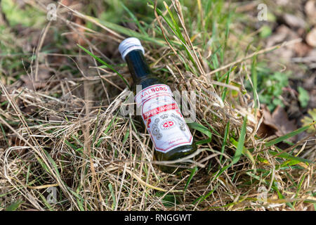 Rød Aalborg ('Red Aalborg'), Taffel Akvavit, small aquavit bottle thrown in the grass by the side of the road; Saeby, Denmark - Stock Image