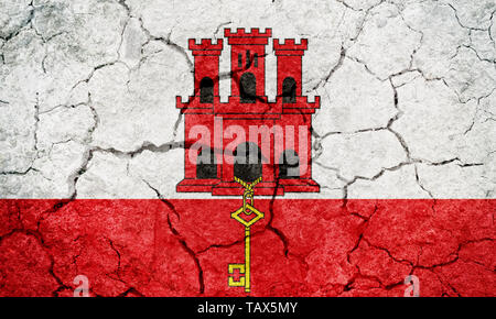 Gibraltar flag on dry earth ground texture background - Stock Image