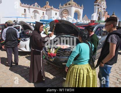 Priest blessing cars, a unique ritual at the Basílica de Nuestra Señora in Copacabana, Bolivia - Stock Image