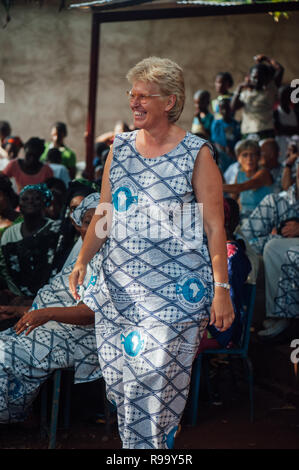 Mature caucasian woman singing and dancing. Multi Ethnic music party to celebrate western and developing countries cooperation. Bamako, Mali. Africa - Stock Image