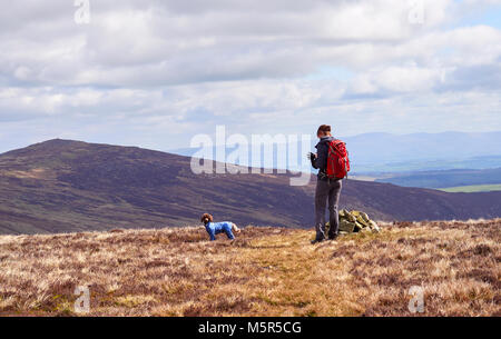 A hiker checking their position on a GPS map at the cairn marking Coomb Height in the English Lake District, UK. - Stock Image
