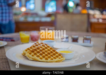 A breakfast plate with Belgian waffles on it. - Stock Image