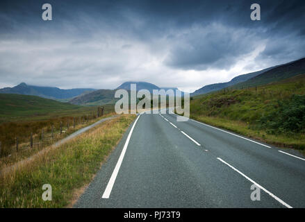 Empty road in Snowdonia National Park, North Wales, with the peaks of the Snowdon mountain range in the distance - Stock Image