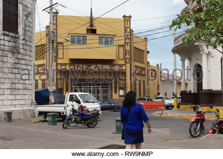 Street intersection in Leon, Nicaragua with cars and a truck and motorcycles with the Gonzales Theater in the center. - Stock Image