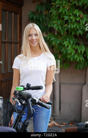 young woman standing outside house entrance with bicycle or bike - Stock Image