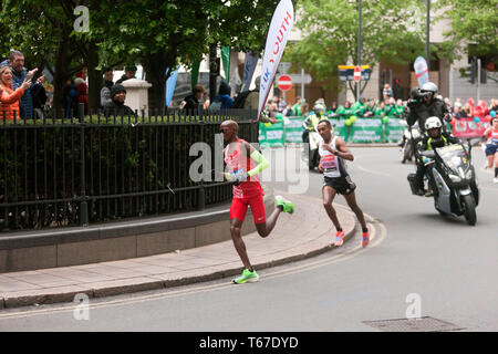 Sir Mo Farah (GBR) running through the North Colonnade, Canary Wharf, closely followed by Leul Gebresilasie (ETH), during the 2019 London Marathon. In the men's elite race, Mo went on to finish 5th, in a time of 02:05:39. Leul was 8th, in a time of 02:07:15 - Stock Image