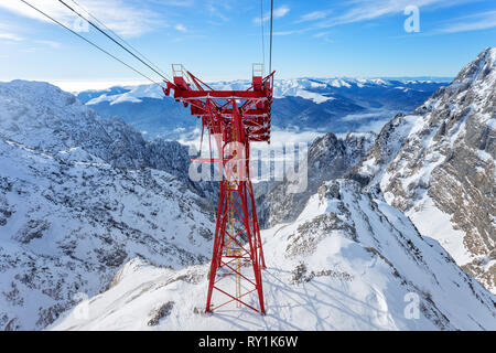 Red Cable Car Pylon and cables way at mountains landscape. Blue sky and massive mountains in background during winter day in ski resort - Stock Image