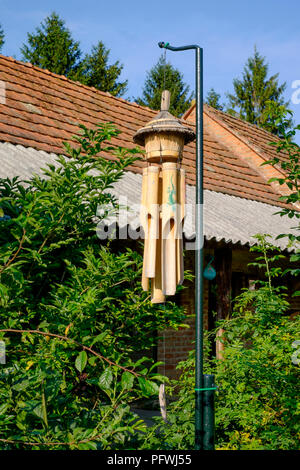 balinese bamboo wind chimes hanging from a pole in the garden of a village house in zala county hungary - Stock Image