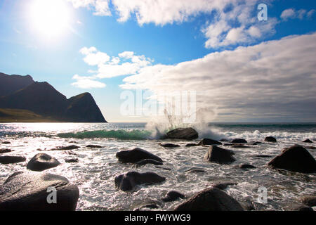 A wave is breaking on a rock on the beach in Unstad on island Vestvågøy on Lofoten in northern Norway - Stock Image