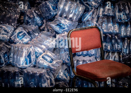 A red chair and and heap of water bottles in a storage area of the cafe on Robben Island, Cape Town, South Africa. - Stock Image