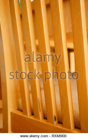 Detail view of a wooden chair back in soft focus. - Stock Image