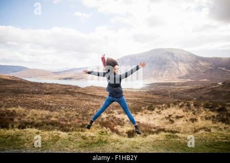 Mid adult woman in mountains doing star jump, Isle of Skye, Hebrides, Scotland - Stock Image