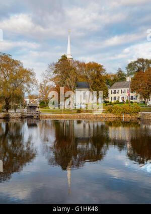View of the town of Sandwich Cape Cod Massachusetts and steeple of the First Church of Christ reflected in the Mill - Stock Image