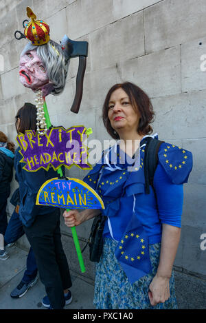 London, UK. 20th October 2018. A woman holds a head of Theresa May with a crown and an axe in it and message 'Brexity Headache? Try Remain'. People gather with placards, banners and flags at Hyde Park Corner for the People's Vote March calling for a vote to give the final say on the Brexit deal or failure to get a deal. They say the new evidence which has come out since the referendum makes it essential to get a new mandate from the people to leave the EU. Peter Marshall/Alamy Live News - Stock Image