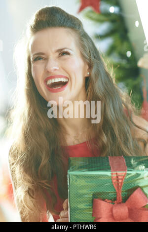 happy trendy woman in red dress with green Christmas present box near Christmas tree - Stock Image
