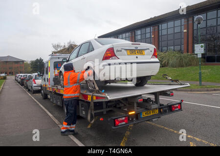 A brokendown car is secured to a recovery vehicle - Stock Image