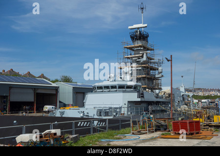 A naval ship undergoing maintenance at the dry dock in Milford Haven - Stock Image