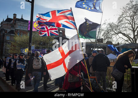 On the day that MPs in Parliament vote on a possible delay on Article 50 on EU Brexit negotiations by Prime Minister Theresa May, the British Union jack, the English Cros of St. George and the EU flag fly over College Green during a protest outside the House of Commons, on 14th March 2019, in Westminster, London, England. - Stock Image