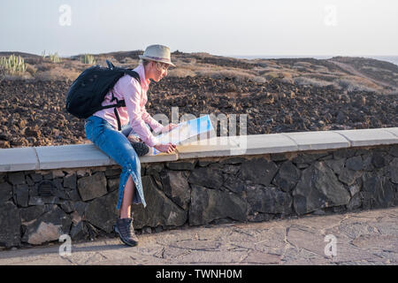 Travel and independence people concept with blonde beautiful adult woman planning the trip with paper map and backpack on his back - outdoor wild dese - Stock Image