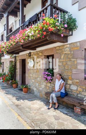 Santillana, Spain - 8th July 2018: Woman sat on bench outside a Posada. A Posada is an inn with accommodation. - Stock Image