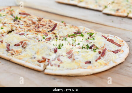Black Forest speciality called Flammkuchen in south Germany and Tarte flambee in northeast France - traditional topping - on wooden platter - Stock Image