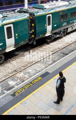 A female platform attendant waiting for a Hitachi Class 800 Intercity Express locomotive train to depart at Paddington Station, London, UK - Stock Image