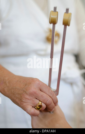Close up of practitioner giving healing tuning fork treatment. - Stock Image