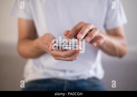 Young man using a touchscreen smartphone cell phone - Hands close-up - Touching, swiping, tapping. Jeans and white t-shirt. - Stock Image