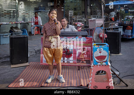 Young girl singing in the street to support her family and accompanied on a keyboard by her blind father. Thailand Southeast Asia - Stock Image