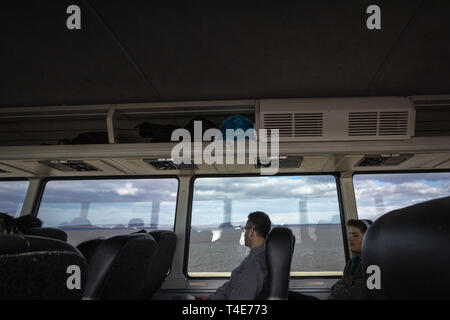 MONTREAL, CANADA - NOVEMBER 10, 2018: Passengers sitting in a coach bus between Montreal and Ottawa, looking at the window of a typical american lands - Stock Image