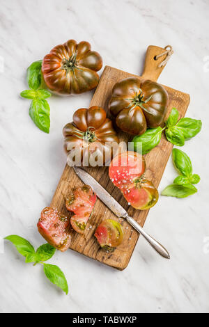 Raw chocolate tomatoes cut in slices on board. - Stock Image